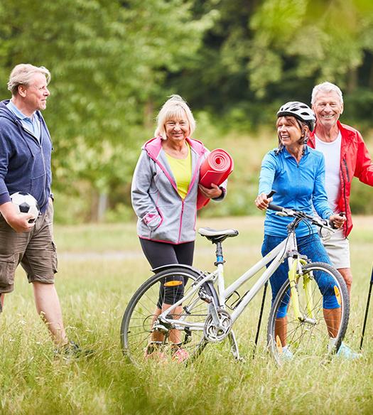 Retired people biking through field