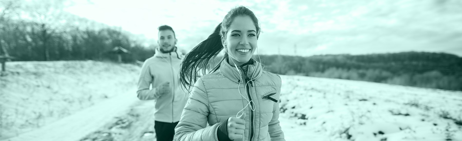 Woman and man jogging in snowy weather