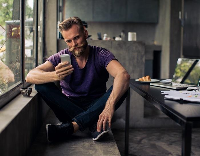 man sitting next to his laptop on his phone