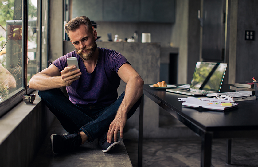 bearded man sitting near work station looking at phone