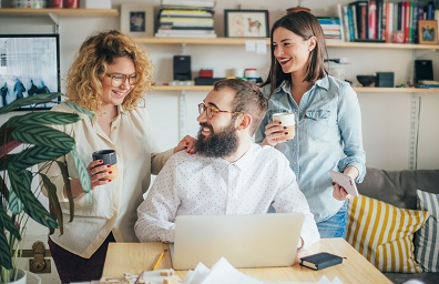 two women helping a man with laptop