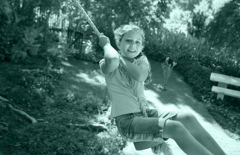 Girl swinging on rope swing