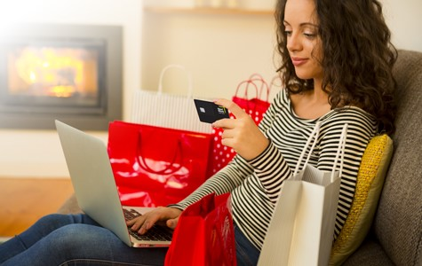 woman shopping online holding credit card