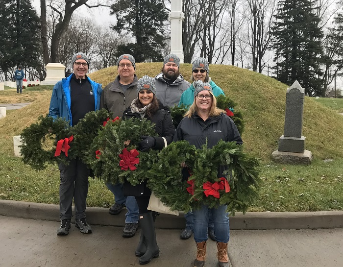 Several men and women holding wreaths