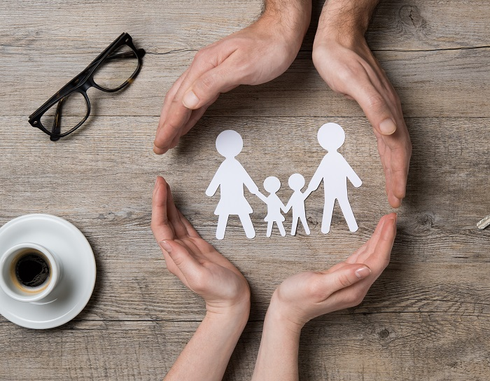 four hands surrounding a paper cutout family