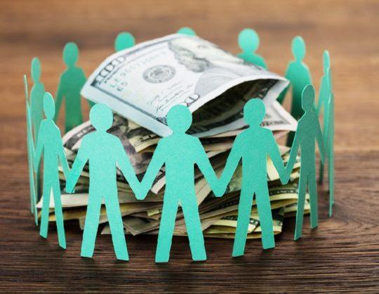 paper cutout of people surrounding cash